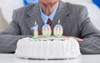 birthday cake with lit candles for a century, one hundredth birthday